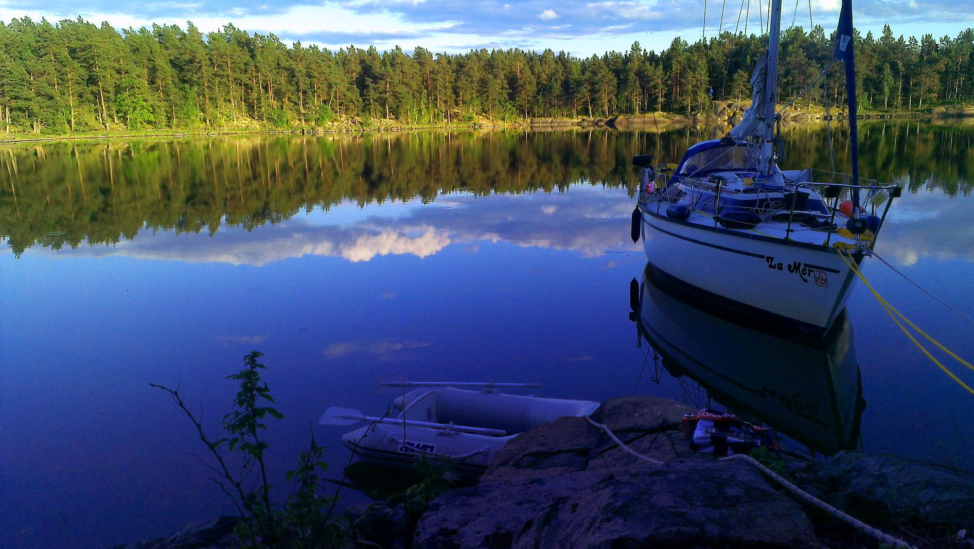 Ein Segelboot liegt in ruhiger Bucht der schwedischen Schären