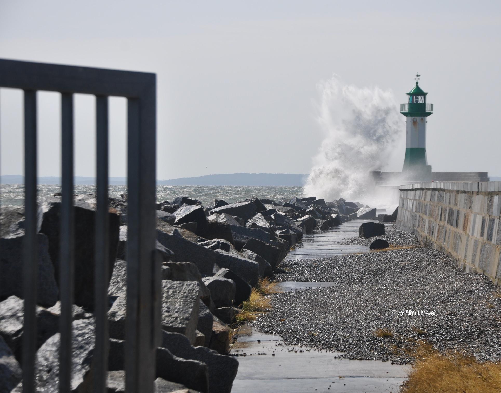Eine große kräftige Welle bricht an einem Leuchtturm Leuchtturm