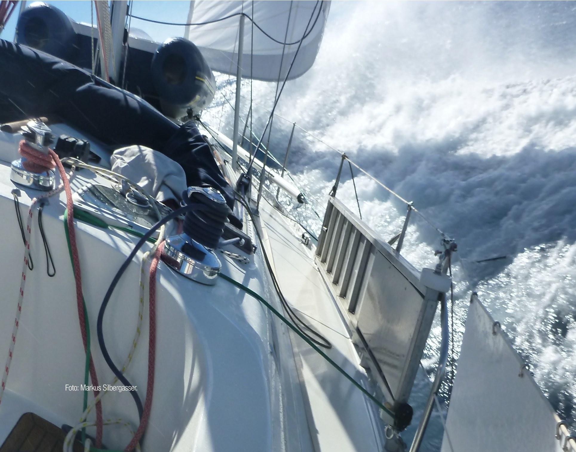 Bild von Gischt, die sich an der Seite einer Segelyacht bricht