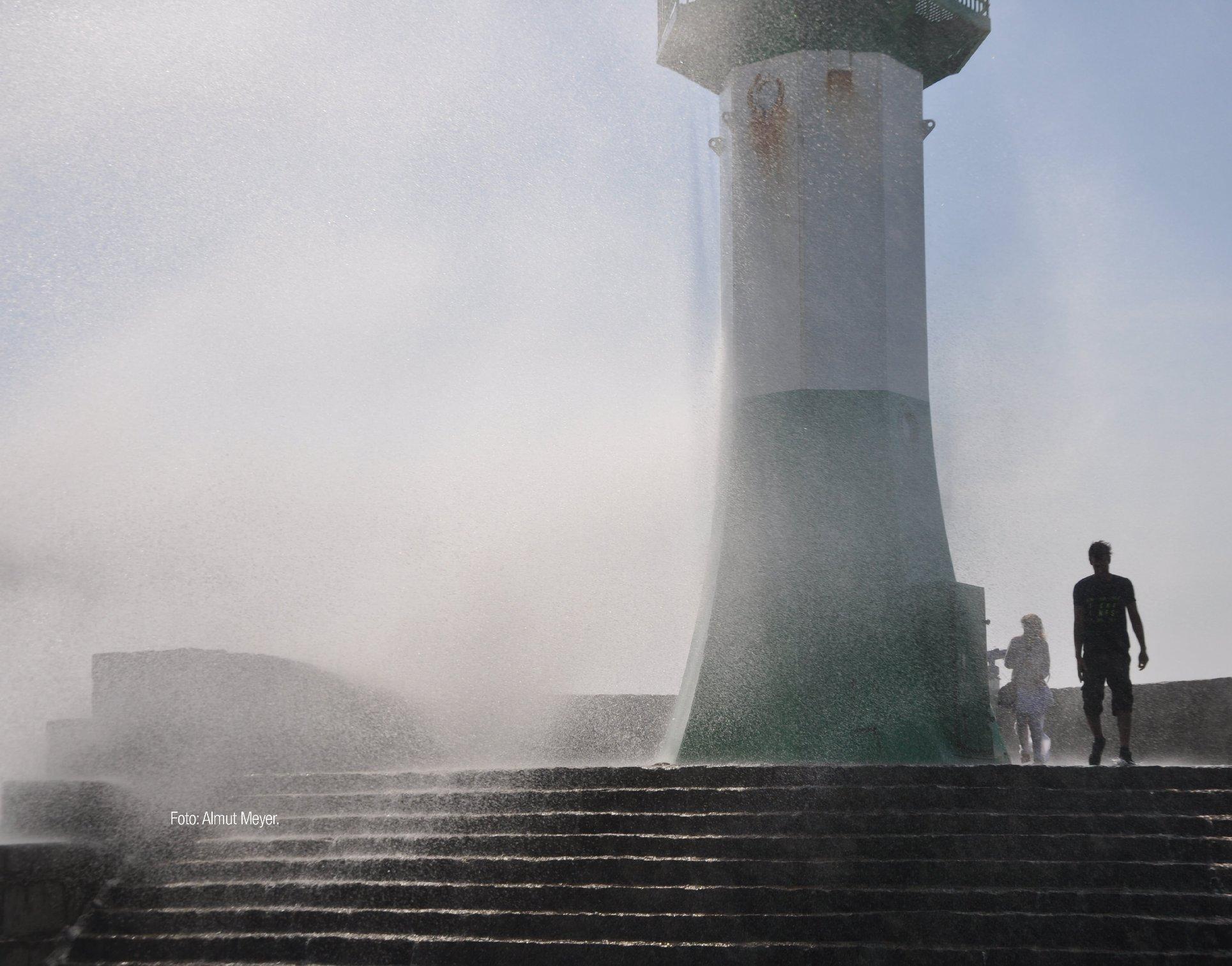Bild einer Wasserfontäne die an einem Leuchtturm bricht